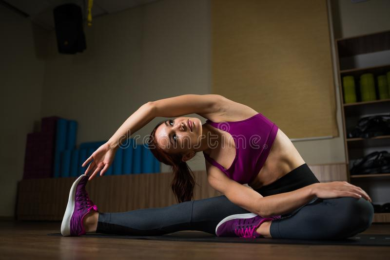 Sporty girl doing stretching on the mat in the fitness hall. royalty free stock image