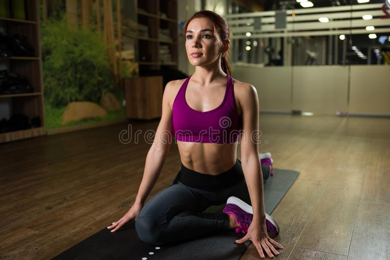 Sporty girl doing stretching on the mat in the fitness hall. stock photography