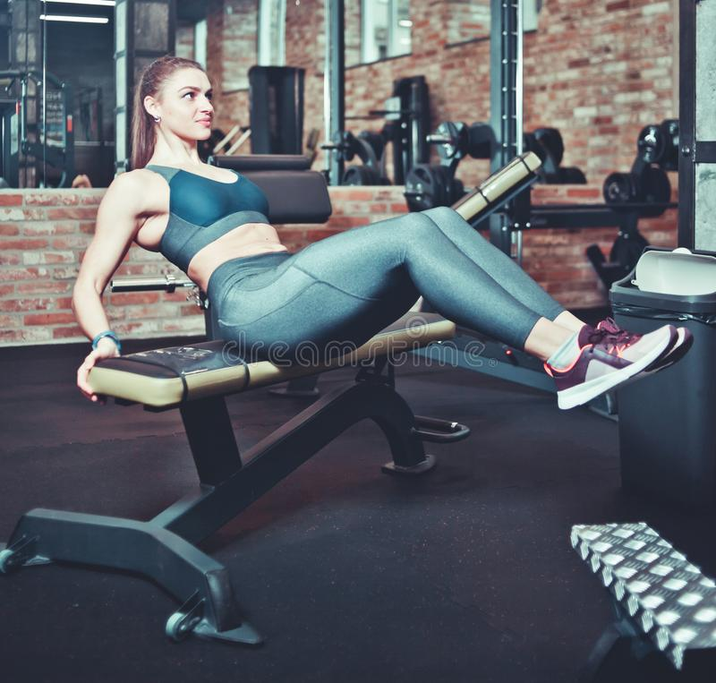 Sporty girl doing v-ups abs workout. At gym, working out concept royalty free stock photos