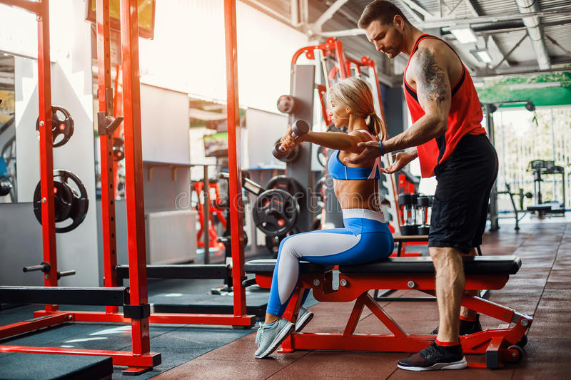 Sporty girl doing weight exercises with assistance of her personal trainer at gym. Sporty girl doing weight exercises with assistance of her personal trainer at royalty free stock images