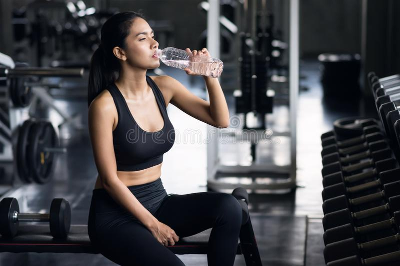 Sporty girl drink water after dumbbell exercise stock image
