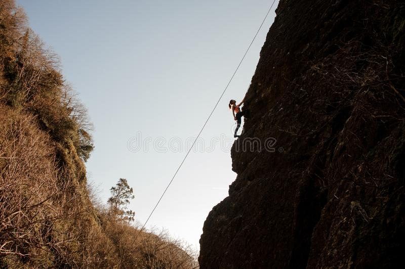 Sporty girl equipped with a rope climbing on the sloping rock and looking up stock images