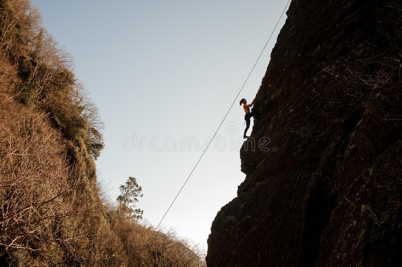 Sporty girl equipped with a rope climbing on the sloping rock royalty free stock image