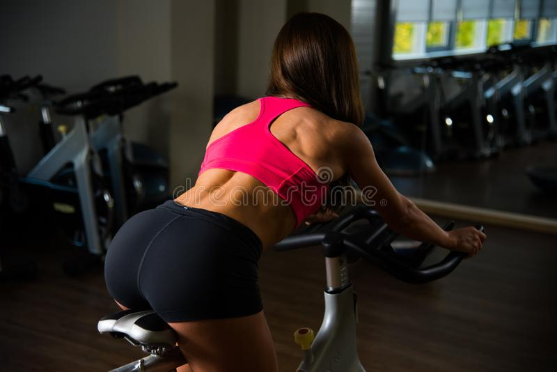 Sporty girl in fitness hall on cycle with background. royalty free stock photography