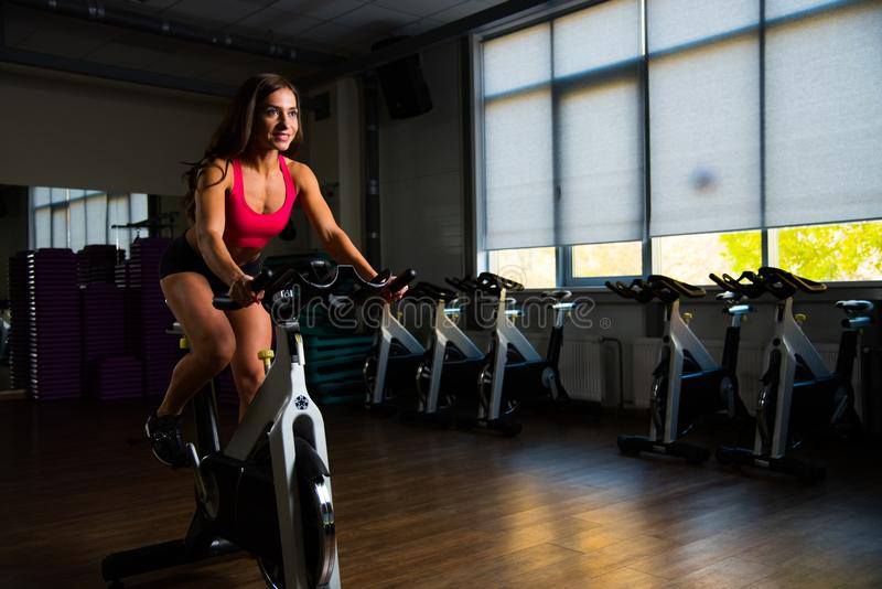 Sporty girl in fitness hall on cycle. stock photos