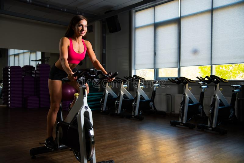 Sporty girl in fitness hall on cycle. stock images
