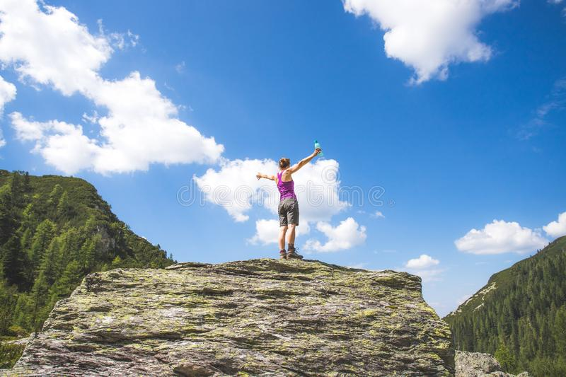 Sporty girl on a hiking trip is standing on a big rock and raises her hands in the air stock image