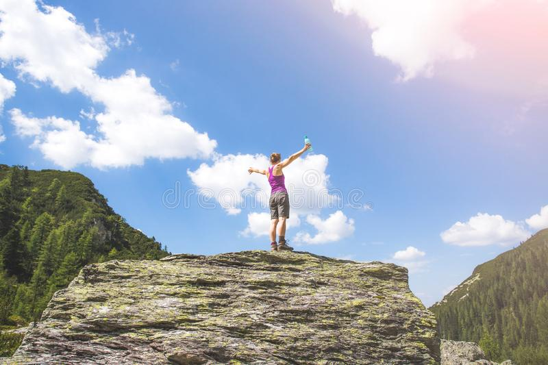 Sporty girl on a hiking trip is standing on a big rock and raises her hands in the air. Target achieved: Sporty girl is standing on a big rock and raises her stock photo