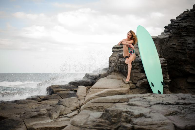 Sporty girl in the multi colored swimsuit sitting near the surf on the rock stock photography