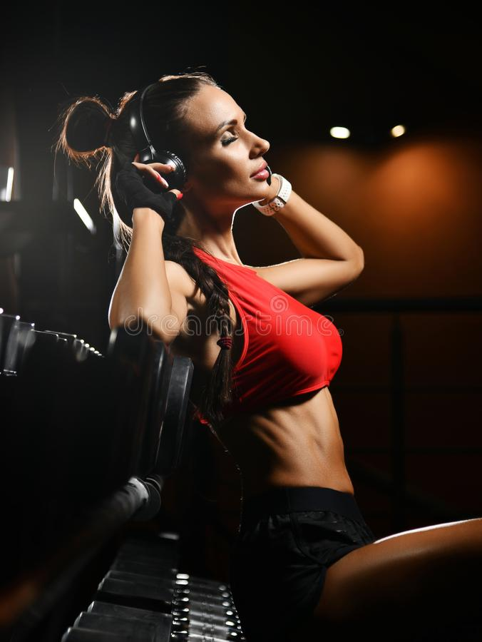 Sporty girl in red and black sportswear is enjoying music during the break in gym. Diet and weight loss concept. Pleased with herself athletic girl in red and royalty free stock photos