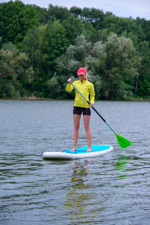 Sporty girl rowing on a SUP board on a big river and enjoy life. Stand on the paddle boarding house - amazing outdoor activities. The Sporty girl rowing on a royalty free stock photos