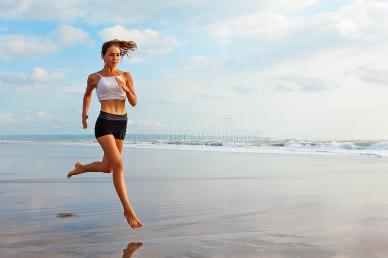 Sporty girl running by beach along sea surf. Barefoot sporty girl with slim body running along sea surf by water pool to keep fit and health. Beach background stock images
