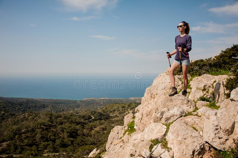 Sporty girl standing on the rock in shorts with walking sticks stock photography