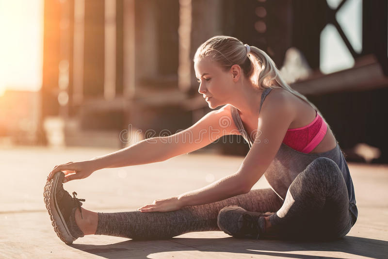 Sporty girl on street. Attractive sporty girl is stretching on street during the sunset stock photos