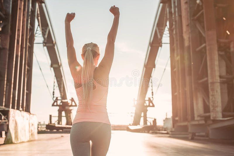 Sporty girl on street. Back view of attractive sporty girl on street during the sunset. Feel of victory stock photo