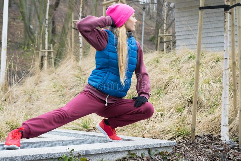 Sporty girl stretching outdoor in park stock photography