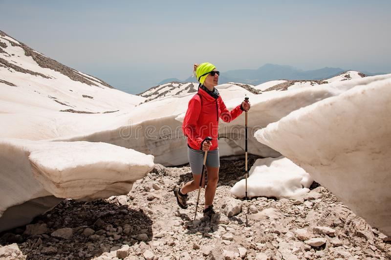 Sporty girl walking on the rocks among the dirty snow with hiking sticks stock photo