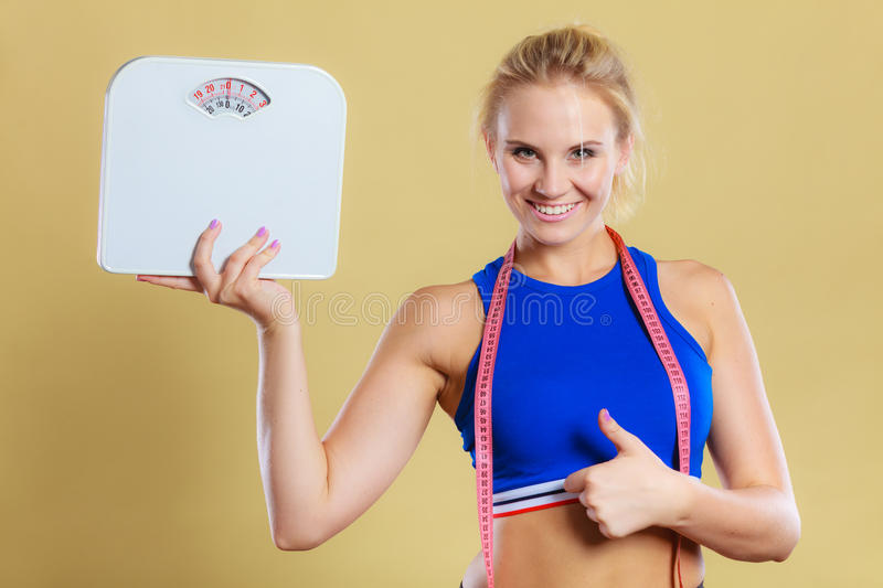 Sporty happy woman with scale, weight loss stock image