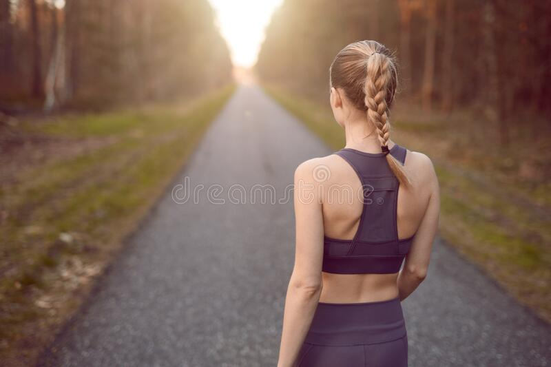 Sporty healthy young woman walking at sunrise royalty free stock images
