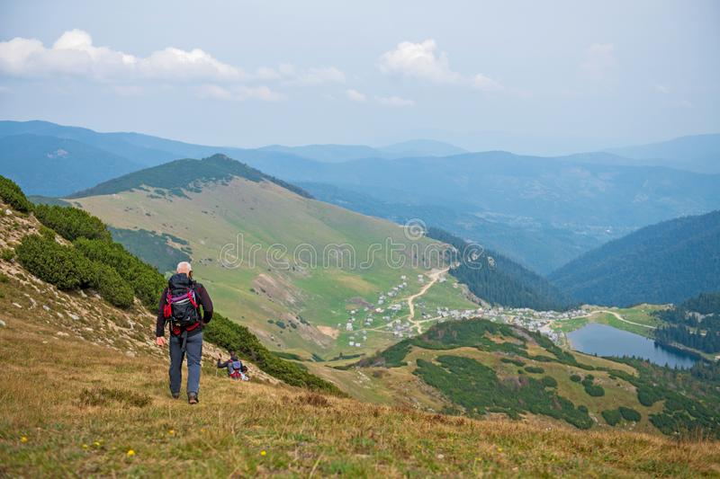 Sporty hikers on path with trekking poles.  stock photography