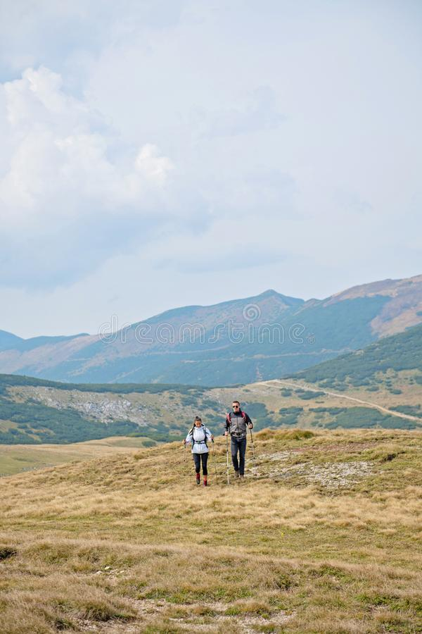 Sporty hikers on path with trekking poles.  royalty free stock images
