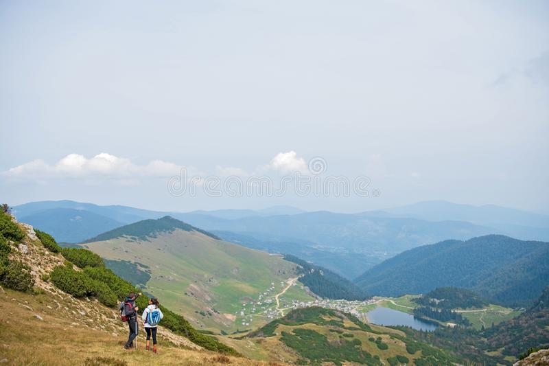 Sporty hikers on path with trekking poles.  stock image