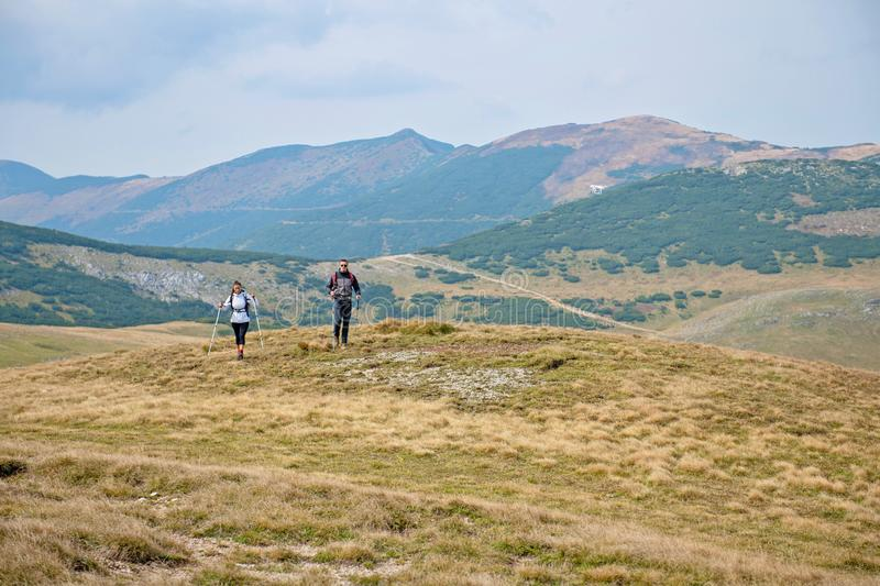 Sporty hikers on path with trekking poles.  stock photos