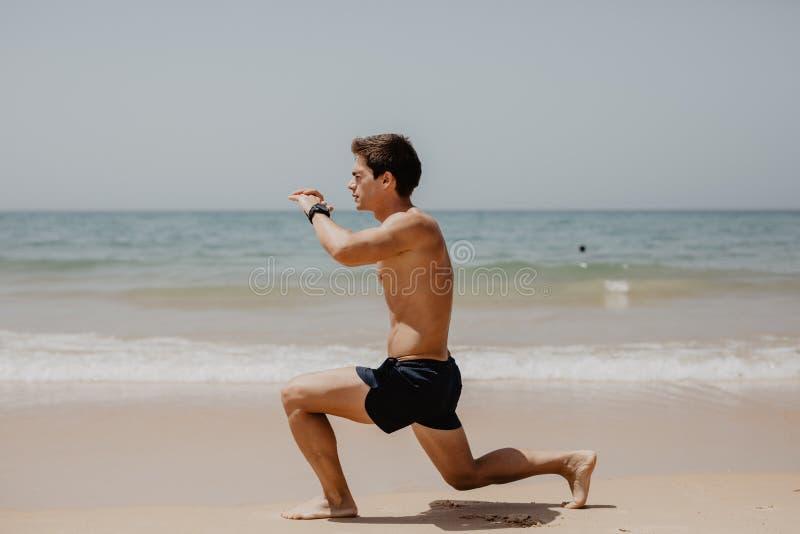 Sporty i zdrowy styl życia Młody człowiek robi chrupnięciom na ocean plaży zdjęcia stock
