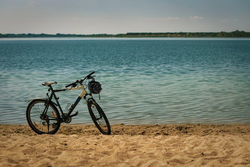 Sporty jechać na rowerze z hełmem na kierownica stojakach na żółtej piaskowatej plaży na brzeg piękny błękitny staw zdjęcie stock