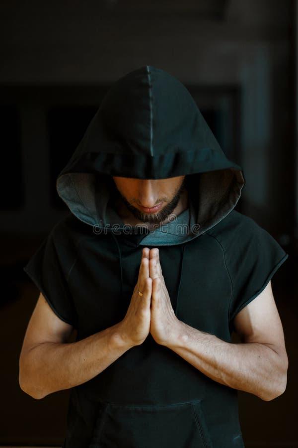 Sporty joga mężczyzna w kapiszonie trzyma jego ręki na ciemnym tle obrazy royalty free