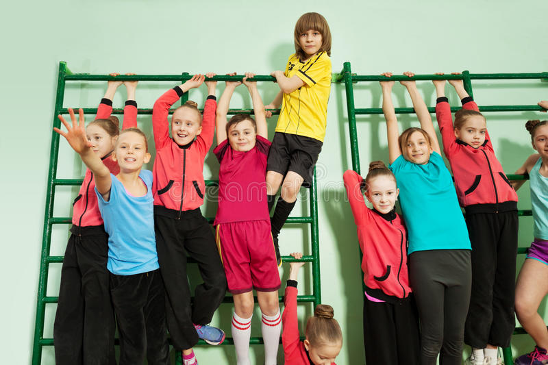 Sporty kids hanging on wall-mounted gym ladder. Portrait of happy 12 years old boys and girls in sportswear hanging on wall-mounted gym ladder stock images