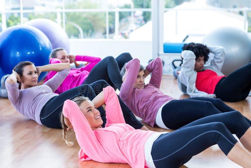 Sporty kobiet robić siedzi podnosi na twarde drzewo podłoga zdjęcie stock