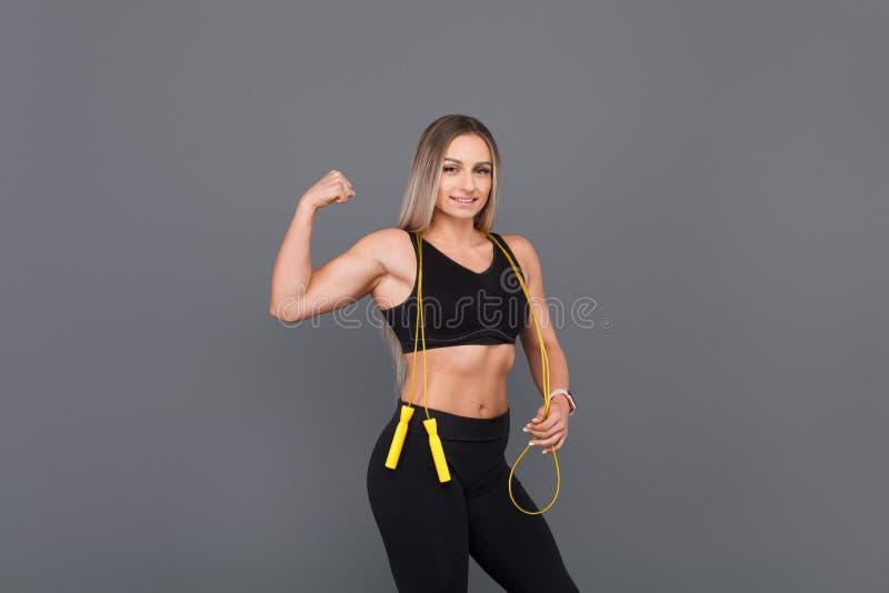Sporty kobieta napina mięśnie trzyma skokową arkanę obraz stock