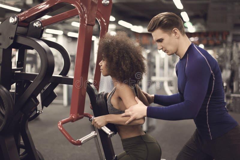Sporty kobieta robi ćwiczeniom pod nadzorem jej osobisty trener w gym fotografia royalty free