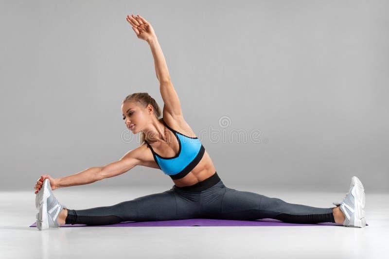 Sporty kobieta robi dratwie i rozciąga ćwiczenie, odosobnionego na szarym tle Piękna dziewczyna robi joga lub pilates ćwiczeniu zdjęcia stock
