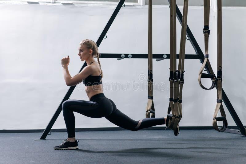 Sporty kobieta robi TRX ćwiczy w gym zdjęcie royalty free