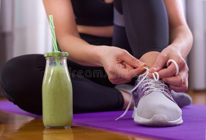 Sporty kobieta wiąże shoelaces na podłoga obrazy stock