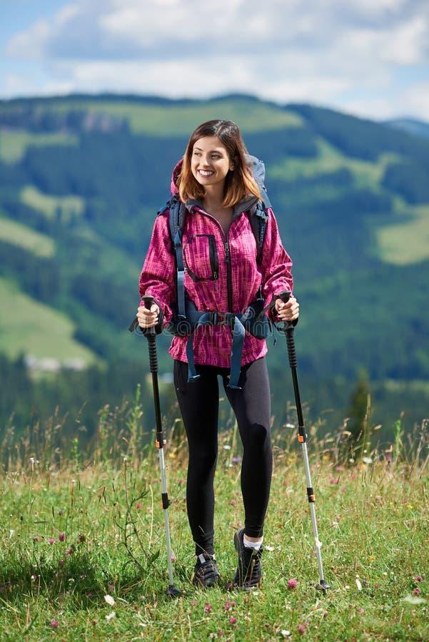 Sporty kobieta wycieczkowicz z plecakiem i trekking wtyka wycieczkować w górach zdjęcie stock