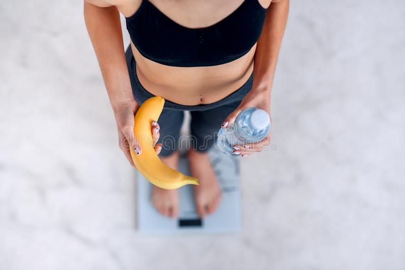 Sporty kobieta z doskonalić ciała ciała pomiarowym ciężarem na elektronicznych skalach i trzymać żółtego banana i butelki zdjęcie stock