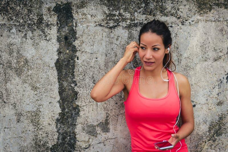 Sporty kobieta z słuchawkami i smartphone fotografia stock