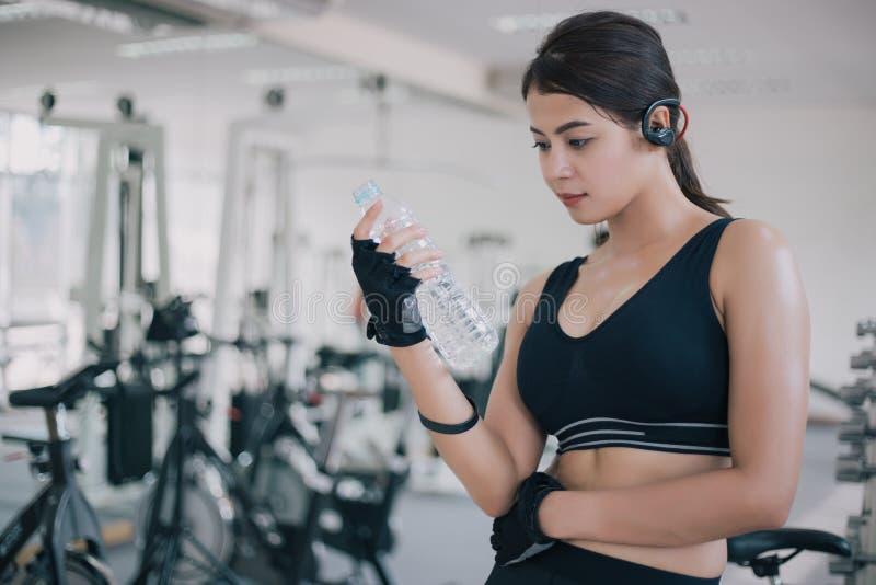 Sporty kobiety Asia woda pitna po ćwiczeń w gym Sprawność fizyczna - pojęcie zdrowy zdjęcie stock