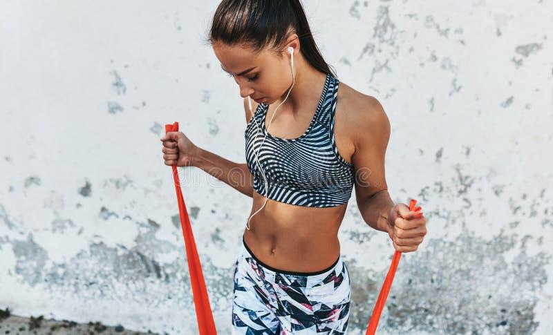 Sporty kobiety pozycja przeciw betonowej ścianie robi rozciąganiu ćwiczy trzymać czerwonego oporu zespołu Sportowa kobieta słucha obraz stock