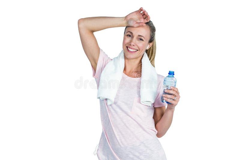 Sporty kobiety wzruszający czoło podczas gdy trzymający butelkę obraz stock
