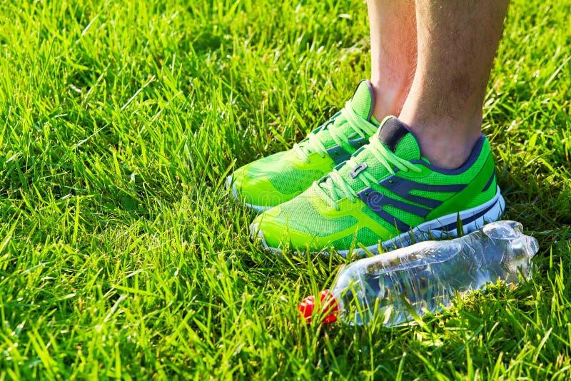 Sporty kują sneakers i butelkę woda na świeżej zielonej trawie fotografia royalty free