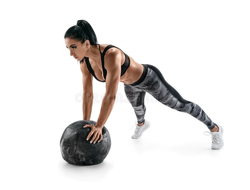 Sporty latin woman doing push ups on med ball. Photo of woman in military sportswear isolated on white background. Strength and motivation royalty free stock photo