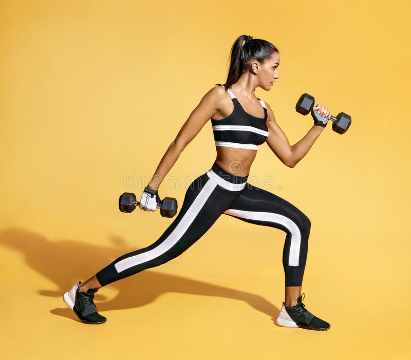 Sporty latin woman training muscles of hands and legs using a dumbbells. Photo of muscular woman in black sportswear on yellow background. Strength and stock image