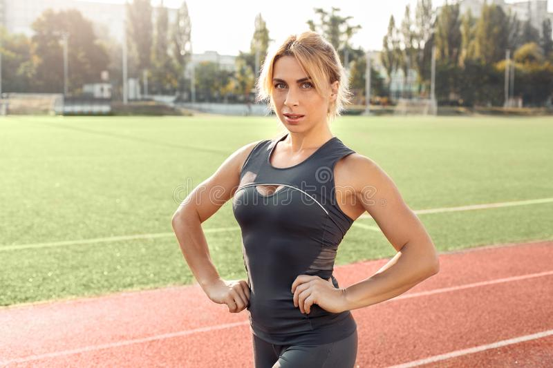 Sporty Lifestyle. Young woman on stadium standing on track hands on hips posing confident royalty free stock photo