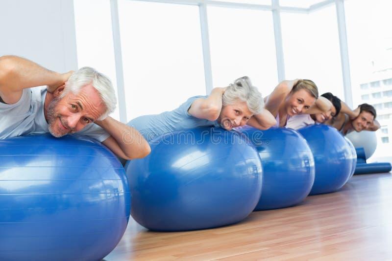 Sporty ludzie rozciąga na ćwiczenie piłkach w gym obrazy stock