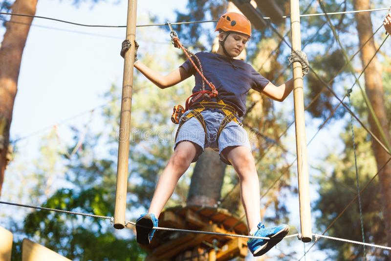 Sporty, młoda, śliczna chłopiec w białej t koszula, wydaje jego czas w przygody arkany parku w hełma i skrytki wyposażeniu w park zdjęcie royalty free