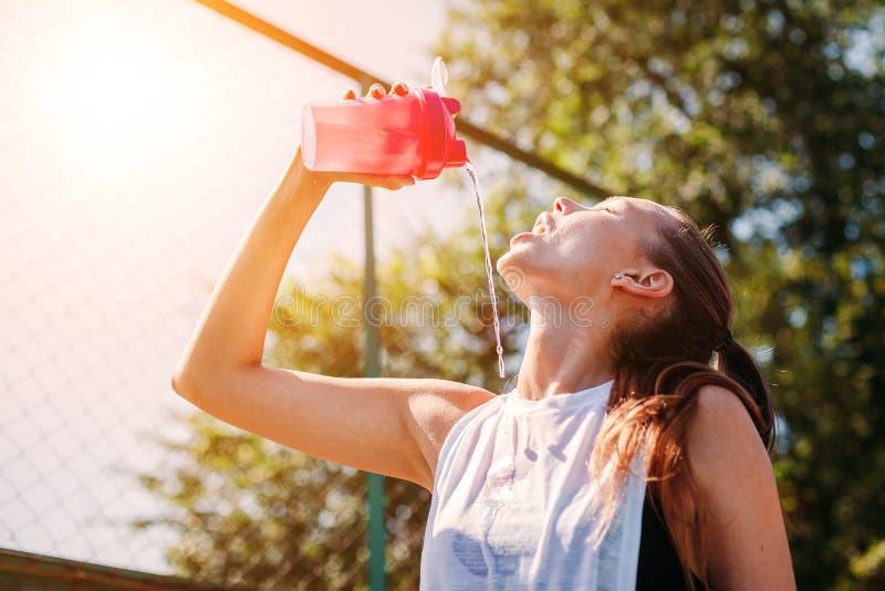 Sporty młoda blondynki kobieta z sporty butelką z chłodno wodą nalewa wodę na ona na sporta polu obrazy stock